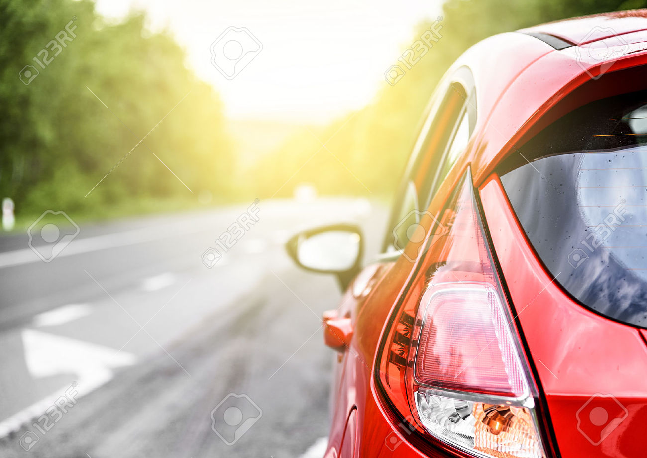 40221650-red-car-on-the-road-at-sunset-stock-photo-street